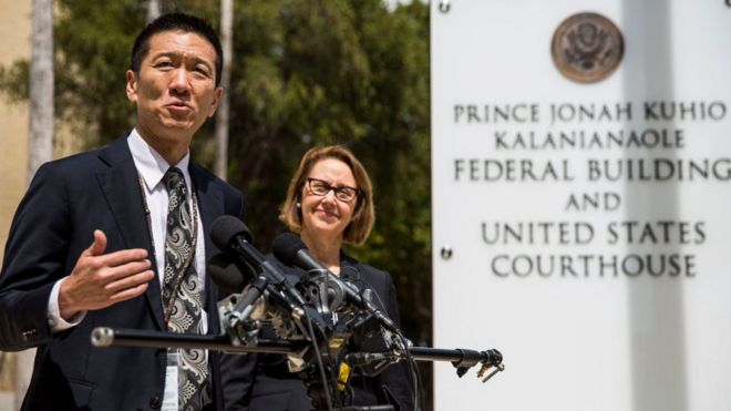 Hawaii State Attorney General Douglas Chin speaks as Oregon Attorney General Ellen Rosenblum looks on at a press conference in front of the Prince Jonah Kuhio Federal Building and US District Courthouse on March 15, 2017 in Honolulu, Hawaii