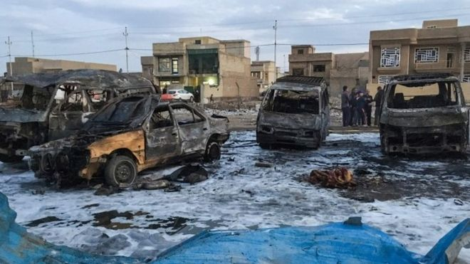 Burnt-out vehicles at the scene of a massive car bomb in a used car market in southern Baghdad (16 February 2017)
