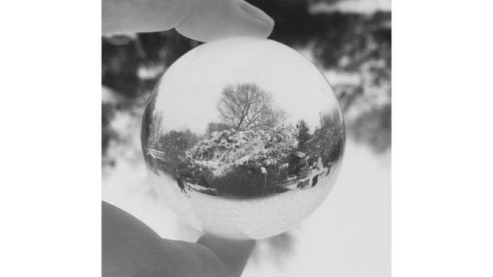 انعكاس حديقة يكسوها الثلج في بلورة