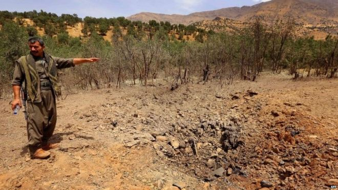 A PKK fighter inspects a crater reportedly caused by a Turkish air strike in the Qandil mountain 29.07.2015