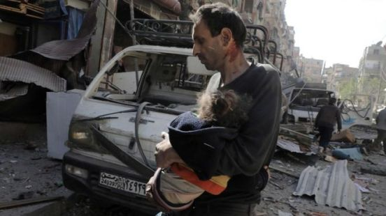 A man carries an injured girl following air strikes on the town of Douma, in the rebel-held Eastern Ghouta region (20 March 2018)