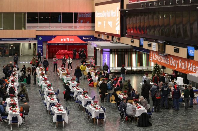 Network Rail volunteers and those from other charities welcome the homeless into the departures and arrivals hall at Euston Station for a Christmas meal