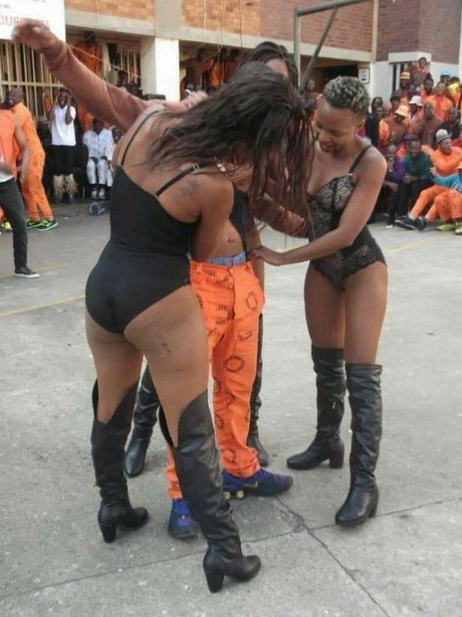 Two women wearing very little entertain an inmate
