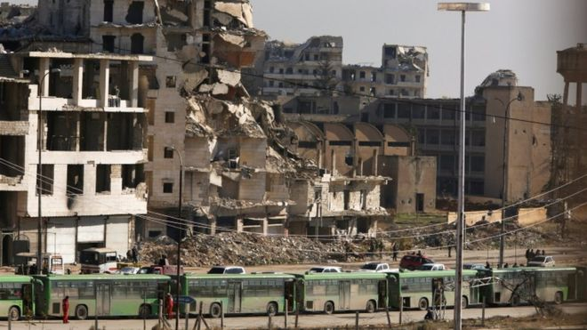 Buses wait in Ramousseh, Aleppo, 15 Dec