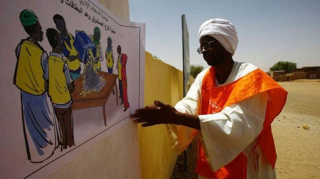 A member of electoral staff display informative posters at the entrance of a polling station in El-Fasher, in North Darfur on April 10, 2016
