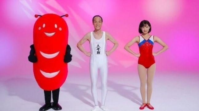 Hideo Higashikokubaru stars with a gymnast (R) and an alien sausage mascot (L)