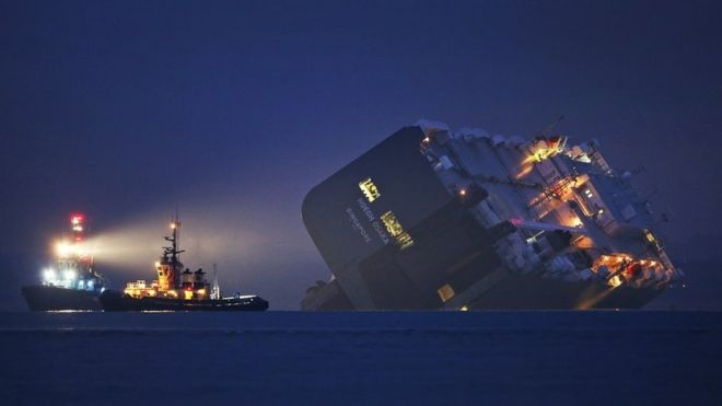 A salvage tug lights the hull of the stricken Hoegh Osaka cargo ship after it ran aground on a sand bank in the Solent in January in Cowes, England.