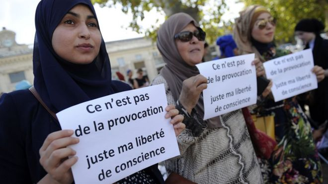 """Women hold signs reading """"Is it not a provocation, just my freedom of conscience"""" during a """"headscarf march"""" in Avignon"""