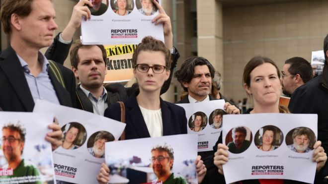 Journalists and activists hold pictures of the Turkey representative for Reporters Without Borders, Erol Onderoglu (R), rights activist Sebnem Korur Fincanci (C) and journalist Ahmet Nesin (R) on 8 November 2016 in front of Cagayan court house in Istanbul as the three campaigners went on trial charged with making terror propaganda for Kurdish militants, as concerns mount over press freedom in the country