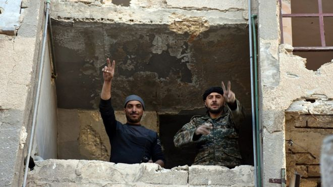 Syrian soldiers making a V for victory sign from a window of damaged building in Aleppo's eastern Masaken Hanano area in Aleppo province, Syria, 27 November
