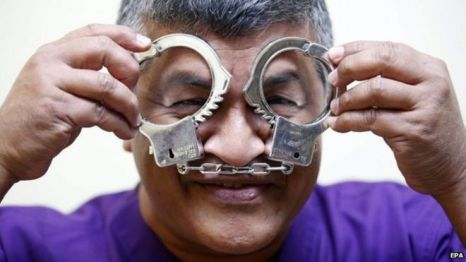 "Malaysian political cartoonist Zulkiflee Anwar Haque, or ""Zunar"", reacts with mock handcuffs during his case at Duta Court, in Kuala Lumpur, 03 April 2015"