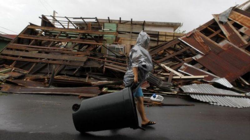 Una mujer camina frente a una construcción derrumbada por María en Fajardo.