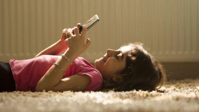 niña usando teléfono móvil