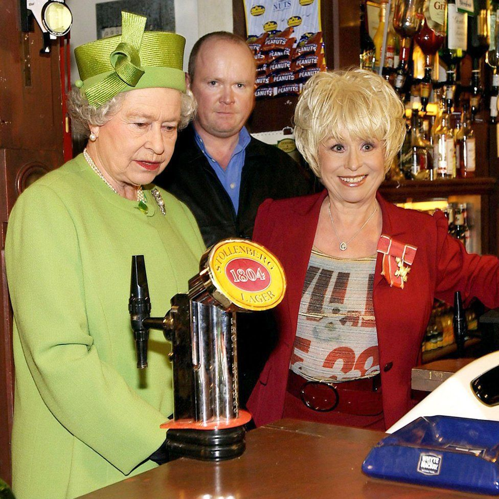 Queen Elizabeth II in the Queen Vic pub during a visit to Elstree Studios where EastEnders is filmed