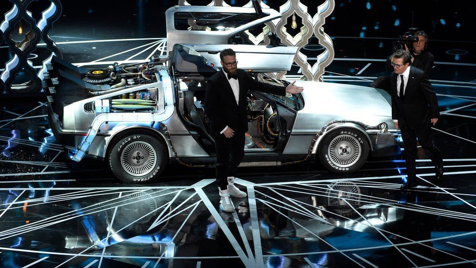 Seth Rogen (left) and Michael J. Fox step out of a DeLorean onstage