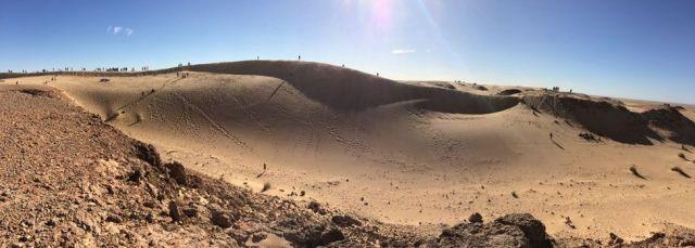 runners in the Sahara Marathon fan across the desert dunes