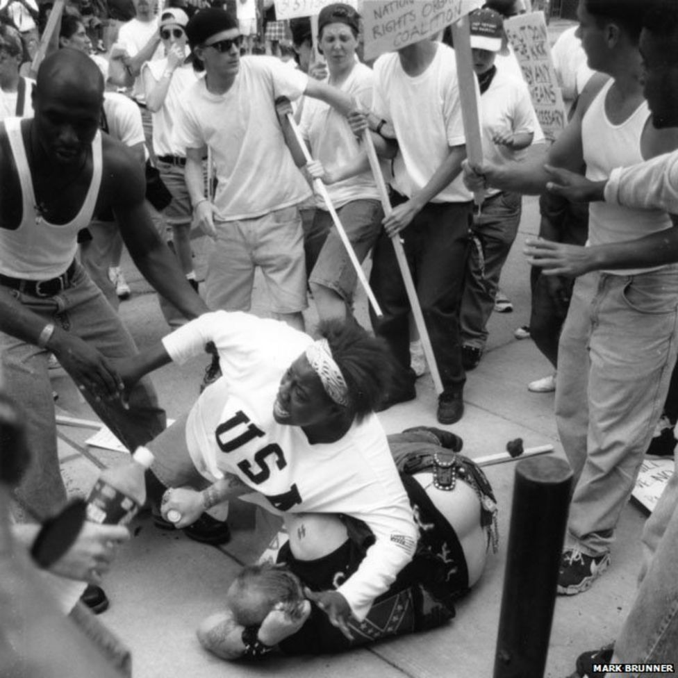 Keisha Thomas shielding a Caucasian man in a Confederate T-Shirt from angry protestors