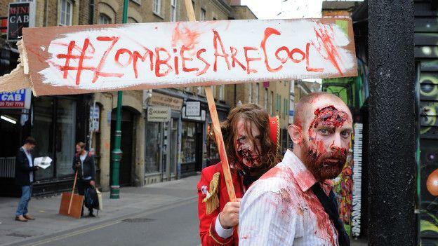 Personas disfrazadas de zombis caminan por las calles de Londres