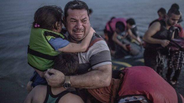 Un inmigrantes llora y abraza a sus hijos tras lograr llegar a las costas de Grecia