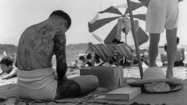 一名山口組成員在海灘上凖備釣魚用具(1955)