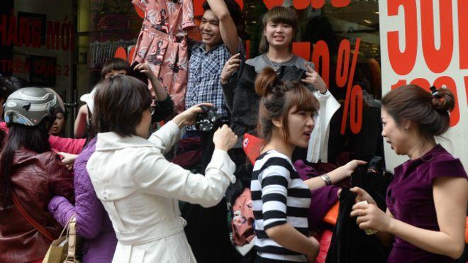 Phụ nữ mua quần áo trên phố