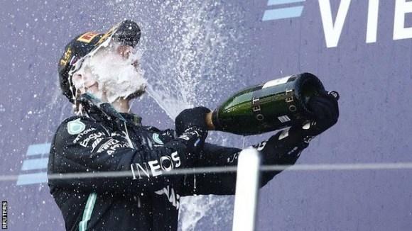 Valtteri Bottas sprays champagne on the podium