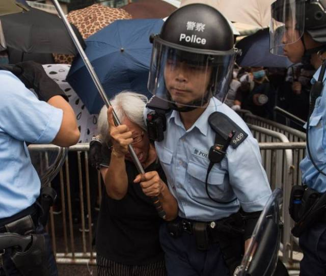A Police Officer Takes A Protester Away From A Demonstration Site During A Rally Against An