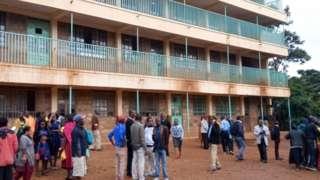 Parents and teachers gather near the scene of a stampede at the Kakamega primary school in Kakamega, Kenya