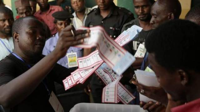 Election officials pull the ballots out of the box at the end of voting in one of the stations in Kaduna, Nigeria - Saturday 28 March