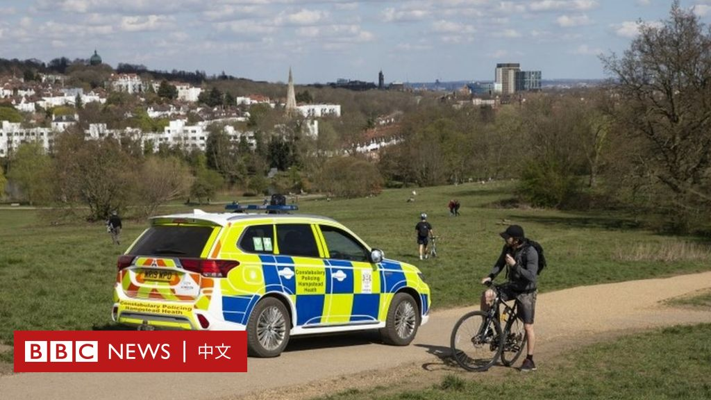 Police speak to a woman sunbathing in a park