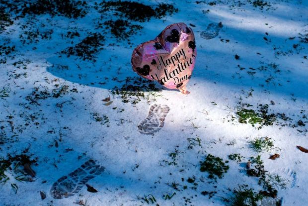 A Valentine's Day balloon floats past footprints in the snow in Houston