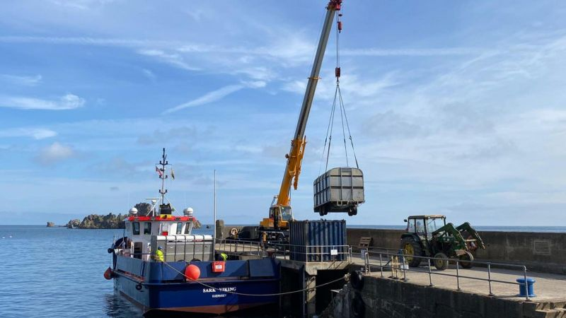 Cows in trailers being lifted off a ferry by crane