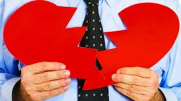 Una persona mostrando un corazón de papel roto