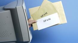 """Mano sale de la pantalla de una vieja computadora con un puñado de cartas en la mano que dicen """"Spam""""."""