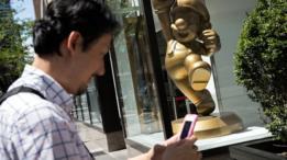 Estatua de Mario Bros frente a las oficinas de Nintendo. Un hombre pasa cerca, aparentemente jugando Pokemon Go.