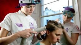 Técnicas aspirando piojos del cabello de una mujer