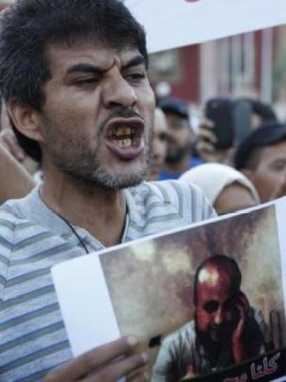 Un hombre sostiene una foto de Mouchine Fikri