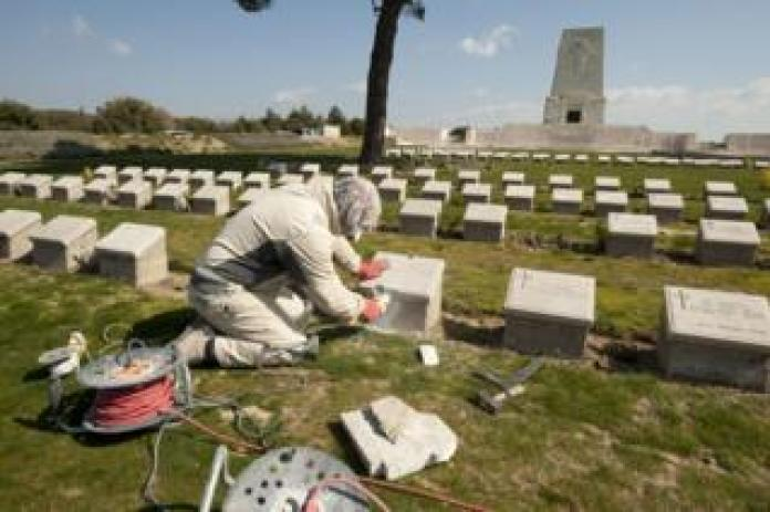A person in a scarf uses power tools to repair a pedestal at Lone Pine Cemetery in Gallipoli, Turkey