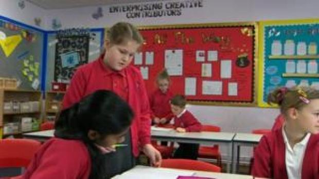 """Pupils in a classroom with """"Enterprising creative contributors"""" written on the wall"""