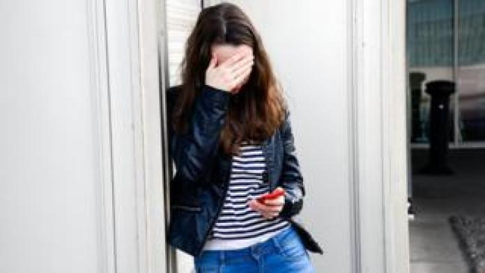 Teenager with hands over her eyes
