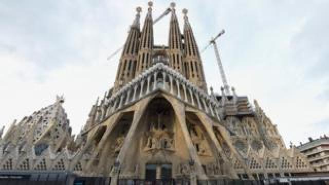 "Tourists walk by the ""Sagrada Familia"" basilica in Barcelona"