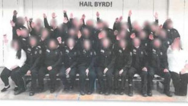 "Employees at the West Virginia Division of Corrections and Rehabilitation giving the salute below a sign that reads ""HAIL BYRD!"""
