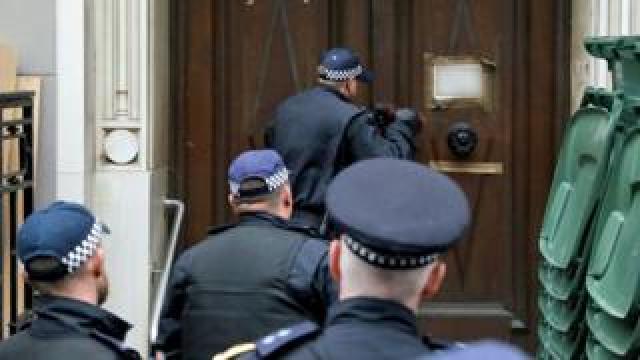 Officers use a battering ram to break down a door