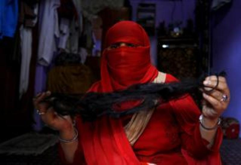 A veiled Kashmiri Muslim woman displays her braid, which was cut off while she was unconscious