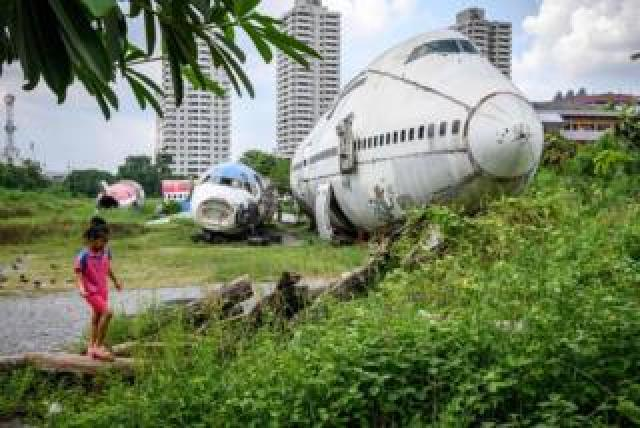 "A child plays in front of abandoned aircraft in the suburbs of Bangkok on 9 October 2019. The area, known as the ""airplane graveyard"", has become a tourist attraction in the Thai capital."