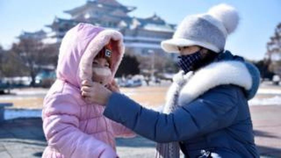 A woman helps her daughter seen wearing a face mask in Pyongyang
