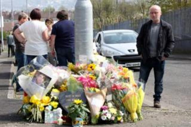 A man looks at floral tributes to Lyra McKee close to where she was shot in Londonderry