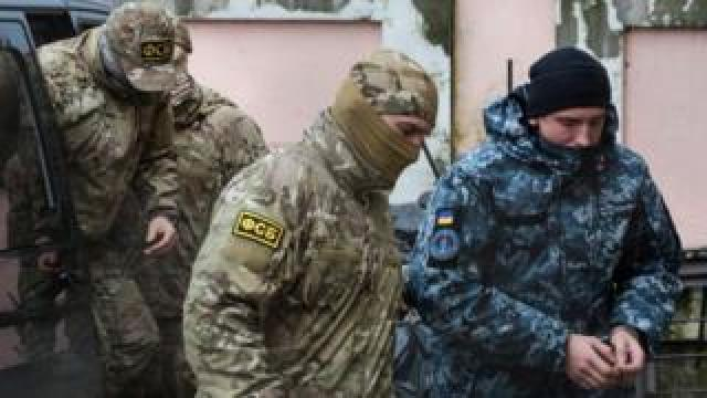 A Russian FSB security service officer escorts a detained Ukrainian sailor to a courthouse in Simferopol, Crimea, on November 27, 2018