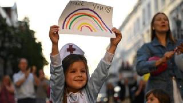 A girl dressed as a nurse holds up a drawing of a rainbow with the words