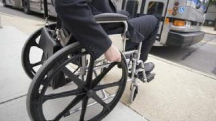 Man in wheelchair waiting for a bus